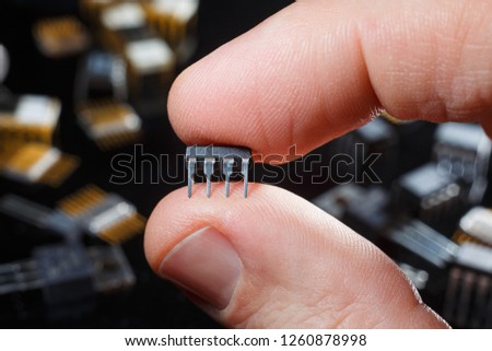 Electronic microcircuit with fingers close-up. Modern technology of electronic components.  #1260878998