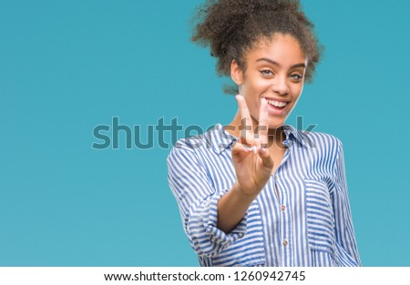 Young afro american woman over isolated background smiling looking to the camera showing fingers doing victory sign. Number two. #1260942745