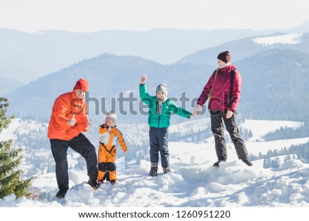 Mother, father and two sons are standing and smiling against the backdrop of snow-capped mountains. Happy family. Winter sunny day #1260951220
