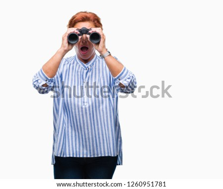 Senior caucasian woman looking through binoculars over isolated background scared in shock with a surprise face, afraid and excited with fear expression #1260951781
