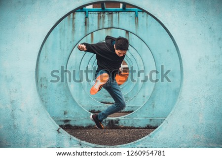 Young Asian active man jumping and kicking action, circle looping wall background. Extreme sport activity, parkour outdoor free running, or healthy lifestyle concept #1260954781
