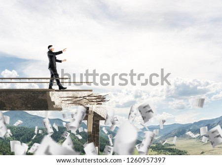 Businessman walking blindfolded among flying papers on concrete bridge with huge gap as symbol of hidden threats and risks. Skyscape and nature view on background. 3D rendering. #1260957397