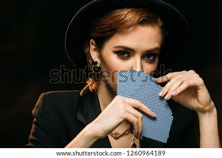 attractive girl in jacket and hat covering face with poker cards isolated on black, looking at camera Royalty-Free Stock Photo #1260964189