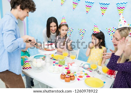 Smiling positive attractive mother in casual shirt standing at table with desserts and cutting cake with knife while content children in party hats eating sweets #1260978922