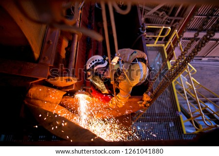 Top view pic male rope access welder wearing full body safety equipment harness abseiling working on fall restraint fall protection position commencing Oxy-Acetylene cutting construction mine site