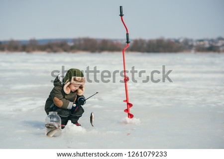 boy fishing on winter. Cute boy catches fish in the winter lake. Winter. Outdoor