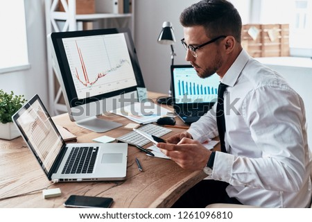So busy. Young businessman in formalwear using smart phone and analyzing data using computer while sitting in the office #1261096810