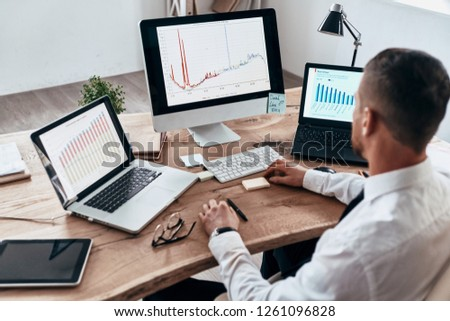 Analyzing sales pitch. Top view of young businessman in formalwear analyzing data using computer while sitting in the office             #1261096828