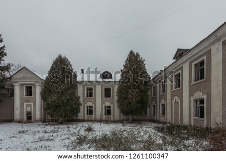 Ruined abandoned old mansion facade in winter. #1261100347