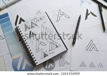 Graphic designer drawing sketch design creative Ideas draft Logo product trademark label brand artwork. Graphic designer studio Concept. #1261156909