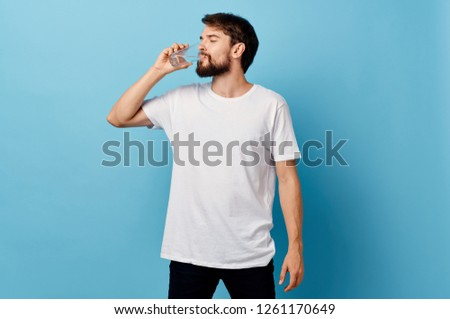 A man in a t-shirt and trousers on a blue background drinking water from a glass            #1261170649