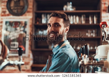 I love my job. Portrait of joyful bearded man in apron looking at camera and smiling #1261181365