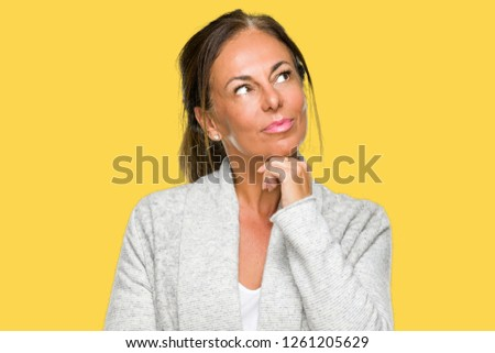 Beautiful middle age adult woman wearing winter sweater over isolated background with hand on chin thinking about question, pensive expression. Smiling with thoughtful face. Doubt concept. #1261205629