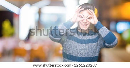 Young handsome man over isolated background doing ok gesture like binoculars sticking tongue out, eyes looking through fingers. Crazy expression. #1261220287