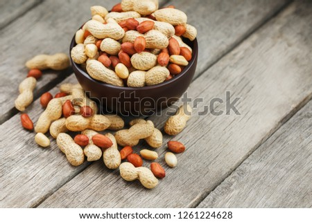 Roasted peanuts in the shell and peeled in a cup, against a gray wooden table #1261224628