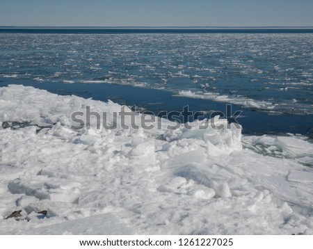Snow and jagged piles of ice float in open water and pile up along the shore of Lake Superior in Northern Minnesota in the USA. #1261227025