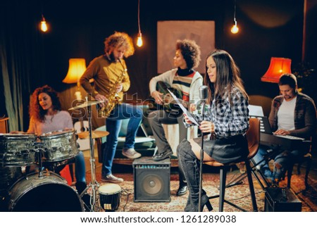 Band practice in home studio. Woman singing while rest of the band playing instruments. #1261289038