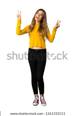 A full-length shot of a young girl with yellow sweater smiling and showing victory sign with both hands on isolated white background #1261332511
