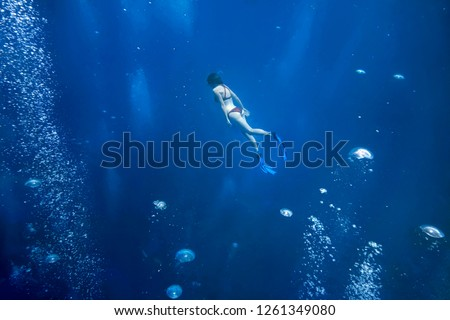 Young snorkeler woman diving at Maldives reef.