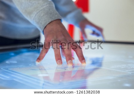 Man hand interacting with large touch screen in museum exhibition Royalty-Free Stock Photo #1261382038