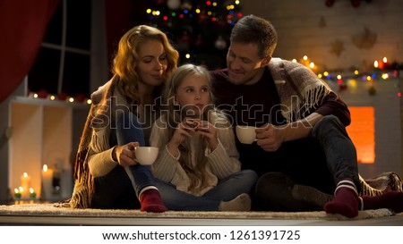 Family drinking hot coffee with cookies near Christmas tree, miraculous day #1261391725