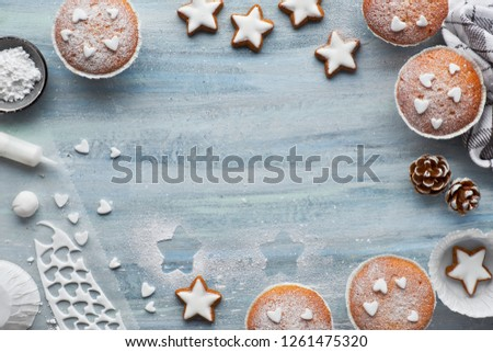 Top view of the table with sugar-sprinkled muffins, fondant icing and Christmas star cookies on blue wooden board with copy-space #1261475320