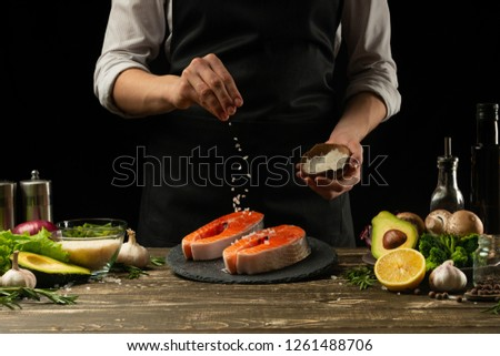 The chef prepares fresh salmon fish, smorgu trout, sprinkling salt with the ingredients. Frost freezing in the air. Preparing to cook fish food. Salmon steak. Woman cook #1261488706