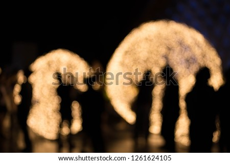 Silhouette photo of people and huge Christmas ball on street. Fashion Woman Night City, Christmas decorations in the city