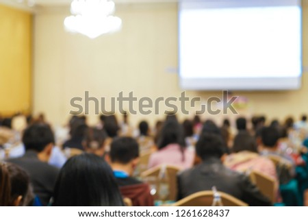 Blurred bokeh group of people sitting in seminar conference room with white screen #1261628437