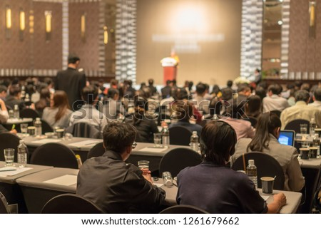 Rear view of Audience wearing and listening Speakers via Interpreter Headset on the stage in the conference hall or seminar meeting, business and education about investment concept Royalty-Free Stock Photo #1261679662