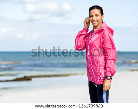 Sporty woman with earphones on the sea coast #1261739860