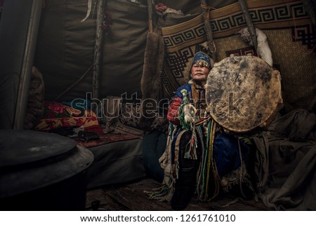 Mongolia shaman doing authentic ritual of summoning spirits. shaman with jewelry holding drum with incense. Shamanic ritual in winter. Ethnic traditions #1261761010
