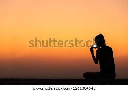 silhouette of young woman taking photo with smartphone at sunset Royalty-Free Stock Photo #1261804543