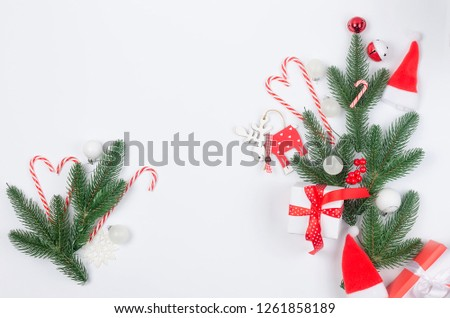 Christmas decorative background with red and white christmas  gifts, ball and toys, fir branches, cones on the white background. card Holiday Concept. copy space, top view. #1261858189