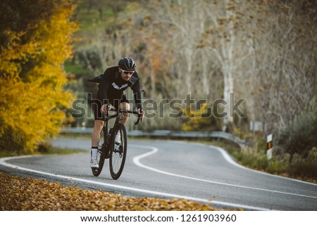 Professional road bicycle racer in action. Men cycling mountain road bike at sunset. #1261903960