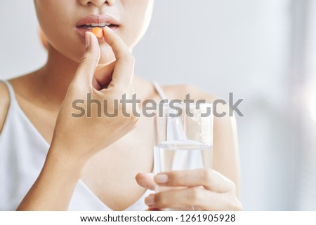 Woman taking tablet with glass of fresh water #1261905928