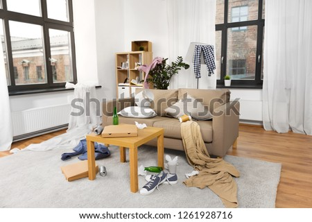 mess, disorder and interior concept - view of messy home living room with scattered stuff #1261928716