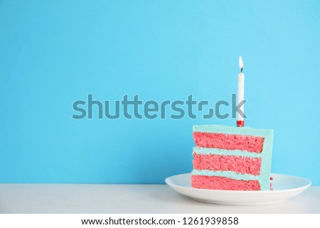Slice of fresh delicious birthday cake with candle on table against color background. Space for text #1261939858