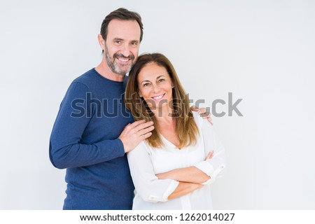 Beautiful middle age couple in love over isolated background happy face smiling with crossed arms looking at the camera. Positive person.