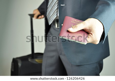 Traveling businessman handing passport - airport security concept