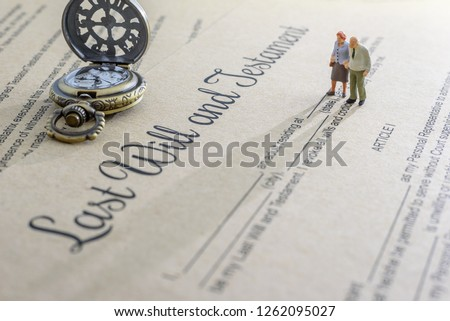 Last will and testament / legacy, inheritance or death tax concept : Miniature elder / old couple stands on a legal document form, depicts preparing to transfer properties to their heirs after death #1262095027