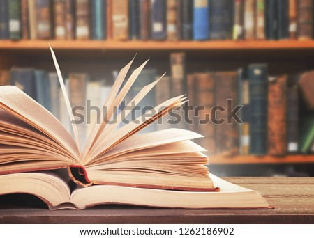 Old open book on a bookshelf background. #1262186902
