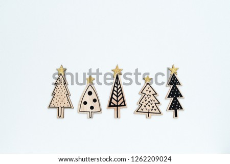 Five carved from wood and painted funny Christmas trees on white background. Happy New Year and Christmas greeting card concept, minimalist flat lay style