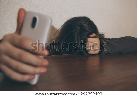 Teen girl excessively sitting at the phone at home. She is a victim of online bullying Stalker social networks - Image #1262259190