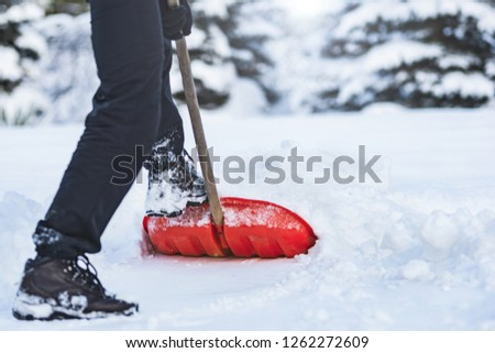 Public service worker or citizen shoveling snow during heavy winter weather #1262272609