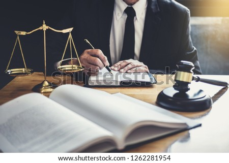 Male lawyer or judge working with contract papers, Law books and wooden gavel on table in courtroom, Justice lawyers at law firm, Law and Legal services concept. #1262281954