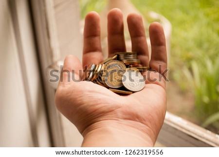 Money in coins in hand. Argentine coins. #1262319556