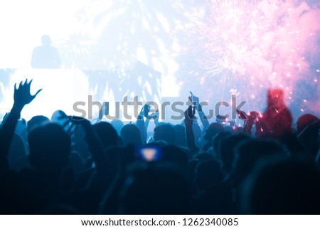 New Year concept - fireworks and cheering crowd celebrating the New Year #1262340085