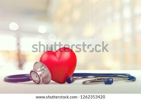 One single alone red heart love shape hand exercise ball with bandage MD medical doctor physician's stethoscope white wood background: Hospital life insurance concept: World heart health day idea Royalty-Free Stock Photo #1262353420