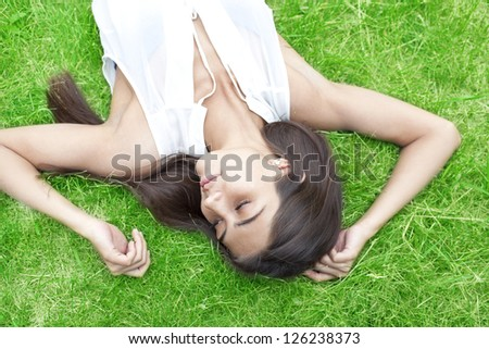 attractive young latin hispanic girl enjoying on green fresh grass  and having fun #126238373
